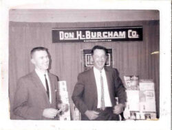 Archive photo of two men lauging in front of Don Burcham Co. logo