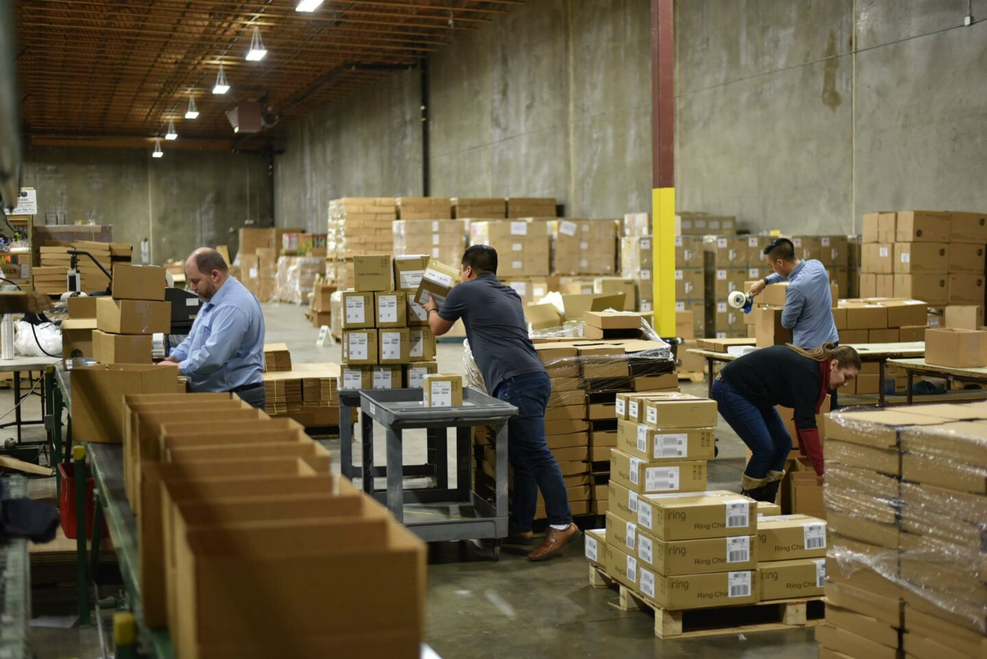 People moving boxes in warehouse