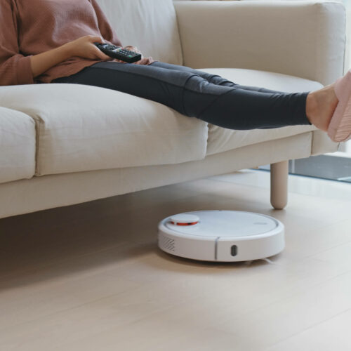 person on couch and robotic vacuum cleaning floor